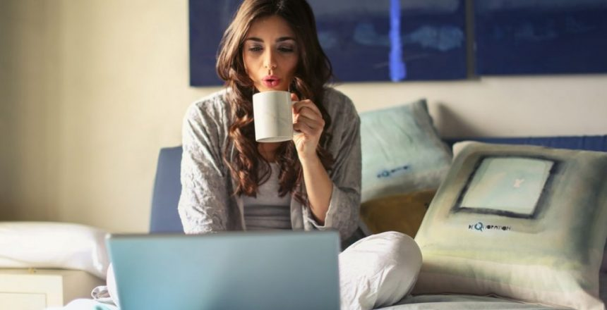 a girl sitting on her bed working with her laptop while drinking from a mug